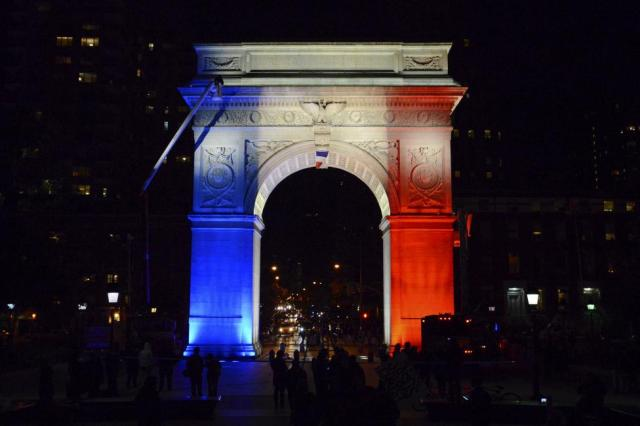 The Washington Arch in Washington Square Park is lit up in blue, white and red, the colors of the French flag, in New York