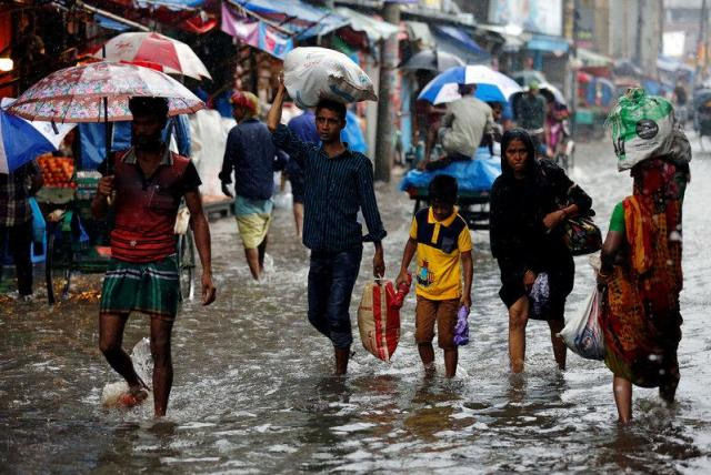 People walk on the water as roads are flooded due to heavy rain in Dhaka